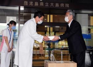 朝山奄美市長(右)からマスクを受け取る県立大島病院の石神院長=12日、奄美市名瀬の同病院前