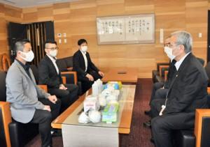 西元さん寄贈のマスクなどを朝山毅市長に届けた重村さん(左)ら=11日、奄美市名瀬