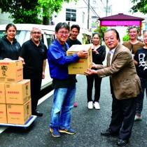 伊東理事長へ高濃度エタノール製品を手渡す川崎杜氏(左から3人目)=27日、奄美市名瀬