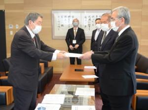 決定した歌詞を答申する田丸委員長(左)=1日、奄美市名瀬