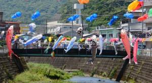 奄美市名瀬の新川上で風になびく色とりどりのこいのぼり