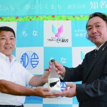 今井町長(左)に自社製の高濃度エタノールを手渡す重信代表(右)=28日、知名町役場