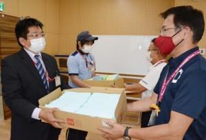 特別定額給付金の申請書が入った封筒を郵便局員に手渡す和泊町の職員(右)=7日。同町役場