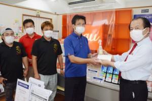 事業者へマスクと消毒液を手渡す和泊町商工会の山田会長(右)=6日、同町