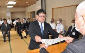 森委員長(右)から当選証書を受け取った8人の新議員ら=25日、大和村防災センター