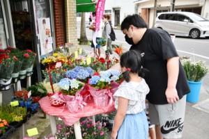 生花店の店先で母の日用のプレゼントを選ぶ来店者=9日、奄美市名瀬