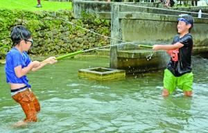 ジッキョヌホーで水遊びを楽しむ子どもたち=21日、知名町