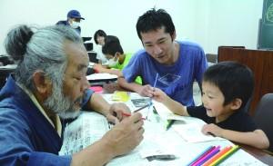 岬さん(左)から絵はがきづくりを教わる親子=21日、奄美博物館