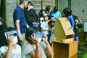 部分日食を観察する小学生たち=21日、与論町