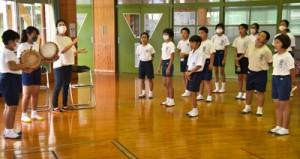 中村さん(左から3人目)と一緒に島唄を歌う児童たち=25日、奄美市笠利町の笠利小学校