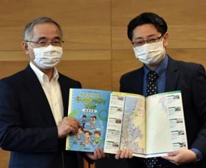 東副市長(左)に冊子を手渡す野末所長=22日、奄美市名瀬