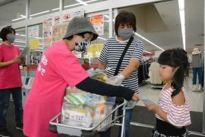 レジ袋削減を促すチラシを配布する会員(手前左)ら=27日、和泊町