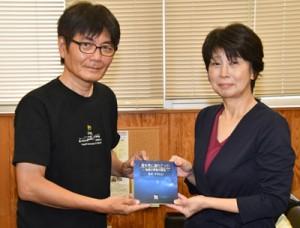 荒木さん(左)から冊子を受け取る奄美図書館の日高館長=23日、奄美市名瀬の県立奄美図書館