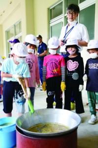 石灰を加えたキビ汁のあく取りに挑戦する児童=4日、大和村の名音小学校