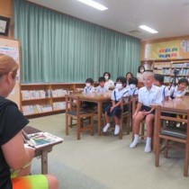 シマグチの読み聞かせに聞き入る佐仁小学校の児童=13日、奄美市笠利町(提供写真)