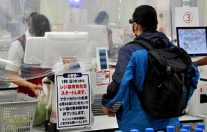 レジ前に案内を張り、1日からレジ袋が有料化されることを周知している店舗=27日、奄美市名瀬