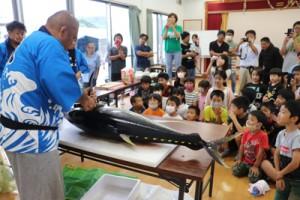 キハダマグロの解体に見入る参加者=21日、喜界町の塩道公民館