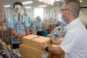 食事券を郵便局に持ち込む町職員=2日、和泊町