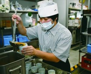 調理作業を行う大島養護学校の生徒=26日、奄美市名瀬