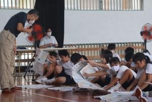 ハザードマップを手に防災意識を高めた児童ら=13日、喜界町の早町小学校体育館