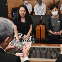 朝山奄美市長(左手前)にチケットの説明をする屋仁川ママの会の会員=1日、市役所