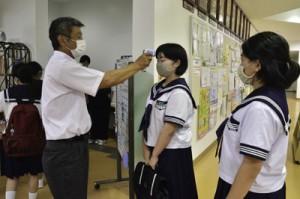 会場入口で体温測定を受ける生徒たち=6日、龍郷町