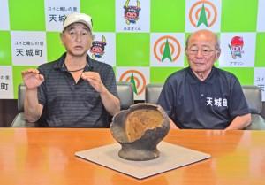 ウンブキ内部で見つかった縄文土器について説明する広部氏(左)と森田町長=23日、天城町役場