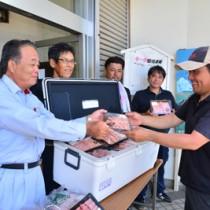 子牛の生産農家(右)に和牛肉を手渡す平山統括理事ら=20日、徳之島町亀津