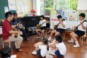 地域から招いた講師から三味線の弾き方を学ぶ児童たち=9日、瀬戸内町の嘉鉄小