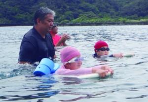 保護者の伴泳でゴールを目指す児童=26日、奄美市住用町
