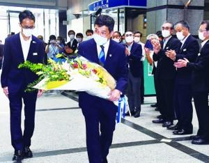 県職員に出迎えられ登庁する塩田知事=28日、鹿児島市の県庁