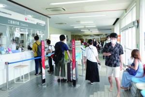 与論島出発の手続きを行う観光客ら=25日、与論空港