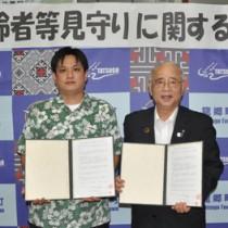 高齢者見守り活動に関して協定を結んだ龍郷町の竹田町長(右)とグリーンストアの里取締役本部長=10日、同町