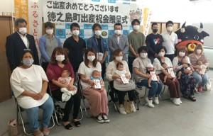 今年度から支給された出産祝い金を受け取った保護者と新生児ら=8日、徳之島町役場
