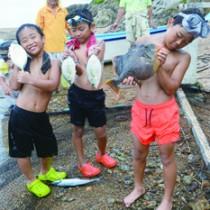 網を小舟に積む作業を手伝う参加児童(下)と網にかかった獲物=12日、宇検村芦検