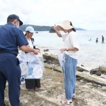 海水浴を楽しむ子どもの保護者らにリーフレットを配る奄美海保職員=5日、奄美市名瀬の大浜海浜公園