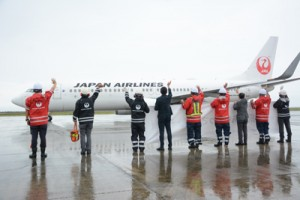 羽田へ向かう航空機に手を振って見送るJALの職員=1日、奄美空港