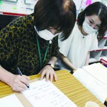 学級PTA会合で、要約筆記者(左)の筆記で、話し合われている内容を確認する大野さん=1日、奄美市の小学校