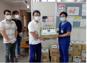 与論ライオンズクラブから職員用の応援物資を寄贈される高杉香志也院長(右)=与論徳洲会病院ホームページより