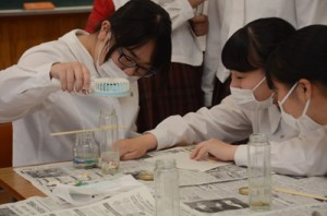 奄美の砂や貝を詰めたキャンドル作りに挑む奄美高校商業科の生徒たち=21日、奄美高校