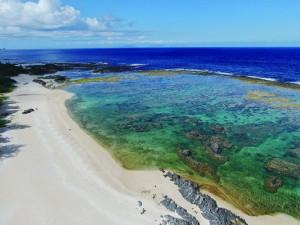 梅雨が明けて青空が広がった徳之島の海辺=20日、徳之島町山の畔プリンスビーチ(本社小型無人機で撮影)