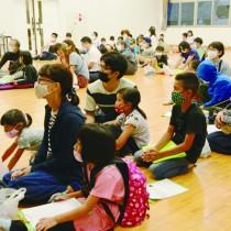 観察会の前にホタルの生態を学ぶ参加者=25日、龍郷町