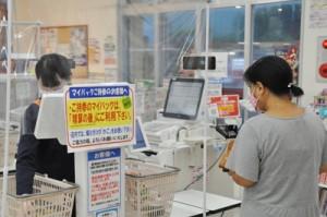 レジ袋の有料化を知らせる案内を張って「エコバッグ活用」などを呼び掛けるスーパー=1日、奄美市笠利町
