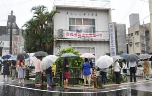 お得な商品券を求め、奄美大島商議所前で傘を差し並ぶ人たち=1日、奄美市名瀬