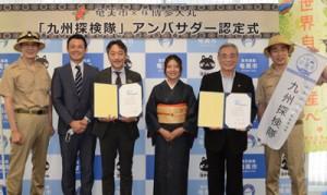 認定証に署名した朝山市長(右から2人目)と万田取締役(同4人目)=3日、奄美市名瀬