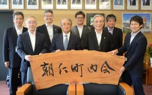 千年松を使った看板が完成し、贈呈を受けた朝仁町内会の屋村会長(前列左から2人目)=13日、奄美市名瀬