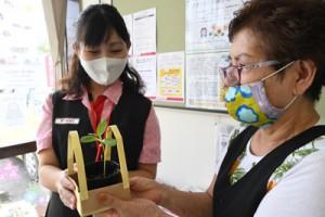 局員(左)から利用客に手渡されるヒマワリの苗=14日、奄美市名瀬の小宿郵便局