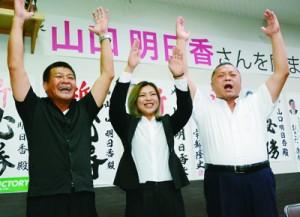 初当選を喜ぶ山口さん(中央)=8月30日午後9時半ごろ、和泊町和泊