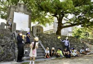 古仁屋小学校敷地内の旧奉安殿前で説明を受ける参加者ら=15日、瀬戸内町古仁屋
