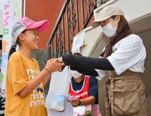 ボランティアスタッフから弁当を受け取る児童ら=17日、瀬戸内町古仁屋
